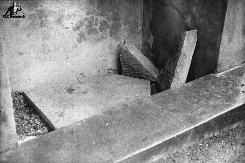 Broken defaced tomb stone at the bottom of Saunière's ossuary in the Rennes-le-Château graveyard that has long been removed.