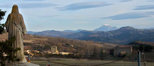 Christ of Antugnac looking at the snowy peak of Bugarach and the hilltop of Rennes-le-Ch6ateau in the distance